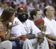 Rapper Rick Ross , second from left, looks on during the second half of Game 2 of an NBA basketball playoff series in the Eastern Conference semifinals between the Miami Heat and the Chicago Bulls ...