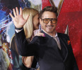 "Cast member Robert Downey Jr . waves next to co-star Gwyneth Paltrow at the premiere of ""Iron Man 3"" in Hollywood"
