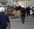 Riot police make their way towards protesters during a protest in Budaiya