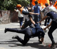 Riot police officer falls while chasing a demonstrator during a protest in Ankara