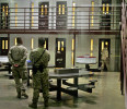 FILE - In this Oct. 9, 2007 file photo, Guantanamo guards keep watch over a cell block with detainees in Camp 6 maximum-security facility, at Guantanamo Bay U.S. Naval Base, Cuba. Guards clashed ...