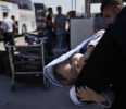 Palestinian woman holds her child as they wait to cross into Egypt, at the Rafah border crossing in the southern Gaza Strip