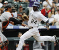 Colorado Rockies' Dexter Fowler, back, scores on a double by Carlos Gonzalez as San Francisco Giants catcher Guillermo Quiroz waits for the throw from the outfield in the fifth inning of the MLB ...