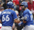 Toronto Blue Jays&#39; Jose Bautista, right, signals to teammate Munenori Kawasaki (66), of Japan , after hitting his second home run of the game against the Boston Red Sox during the sixth inning of a ...
