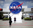 Tourists take pictures of a NASA sign at the Kennedy Space Center visitors complex in Cape Canaveral, Florida