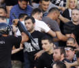 A Serbian riot police officer clashes with Partizan soccer fans during a Serbian National league soccer match Partizan against Red Star, in Belgrade, Serbia, Saturday, May 18, 2013. Thousands of ...