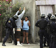 In this April 7, 2013 photo, police frisk a man as they break into a home during a shootout that ended in two suspects killed and one officer injured as police carry out an offensive against gang ...