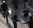 Serbian riot police officer chases Partizan soccer fans before a Serbian National league soccer match Partizan against Red Star, in Belgrade, Serbia, Saturday, May 18, 2013. Thousands of riot ...