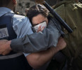 A Jewish orthodox woman prays while Israeli security forces make a human barrier to separate ultra-orthodox Jewish worshippers from the &quot;Women of the Wall&quot; group, not pictured, at the Western Wall ...