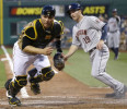 Pittsburgh Pirates catcher Russell Martin, left, looks for the ball as Houston Astros' Robbie Grossman scores on a double steal and a bad throw by second baseman Neil Walker in the fifth inning of a ...