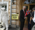 A Greenpeace activist dressed in a polar bear suit looks on as Norwegian Ambassador Knut Hauge greets guests at the Norwegian Embassy in Moscow