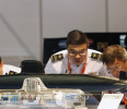 Singapore navy officers scrutinize a model submarine of French builder DCNS at their booth during the IMDEX Maritime Defence Show in Singapore
