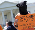 An activist wearing an orange jumpsuit marks the 100th day of prisoners&#39; hunger strike at Guantanamo Bay during a protest in front of the White House in Washington