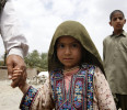 A girl walks with her father after an earthquake in Gosht