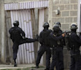 In this April 7, 2013 photo, police break into a home during a shootout that ended in two suspects killed and one officer injured as police carry out an offensive against gang members in Tegucigalpa ...