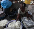 In this photo taken Friday May 3, 2013 a woman produces cassava flour from cassava in a market in Lagos, Nigeria. Scientists say a disease destroying entire crops of cassava has spread out of East ...