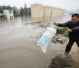 A man throws a sandbag to block the flood water as the storage towers of a petrochemical company were partially submerged after heavy downpours hit Dongshi town of Jinjiang