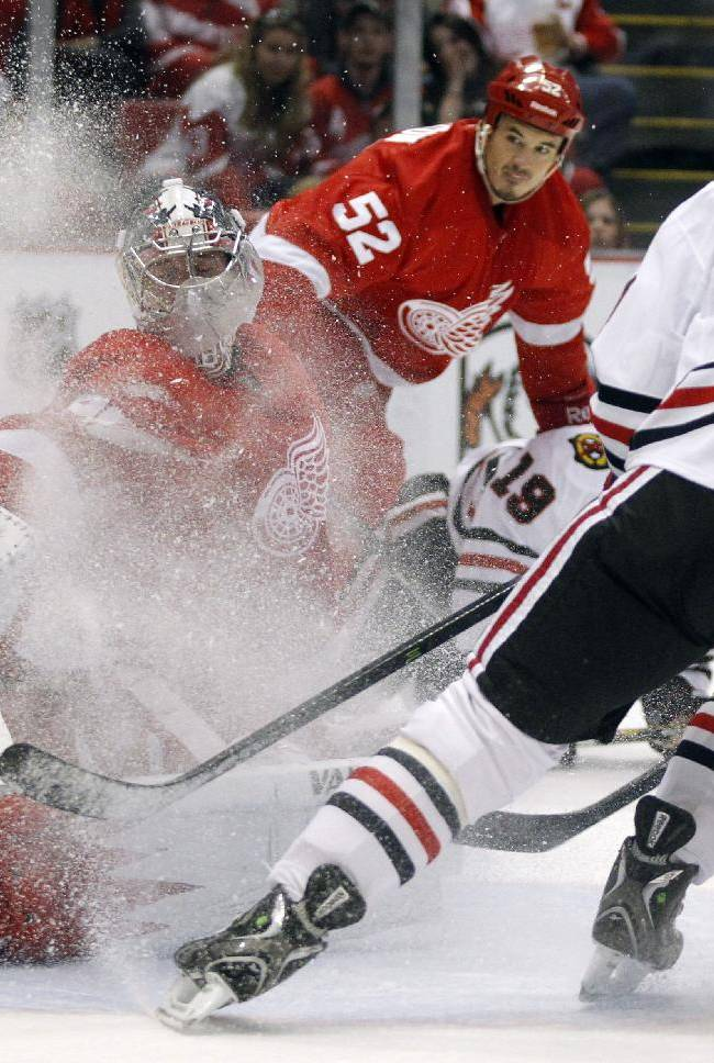 Detroit Red Wings goalie Jimmy Howard, left, reaches out to defend against Chicago Blackhawks' Brandon Saad (20) in the first period of a preseason NHL hockey game Sunday, Sept. 22, 2013 in Detroit