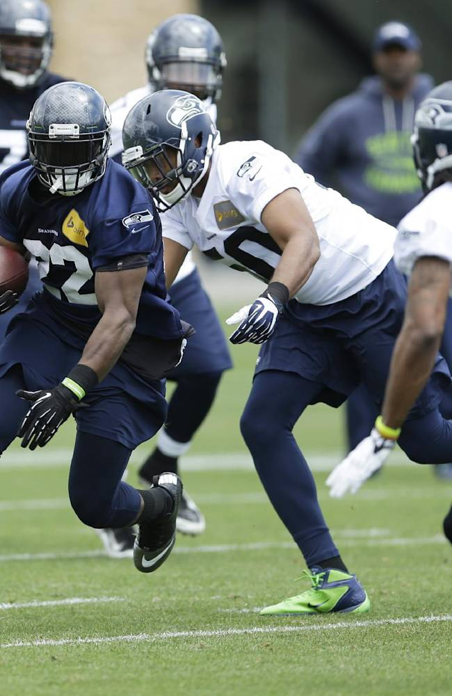 Seattle Seahawks running back Robert Turbin, left, runs the ball during a practice drill at an NFL football organized team activity Monday, June 9, 2014, in Renton, Wash