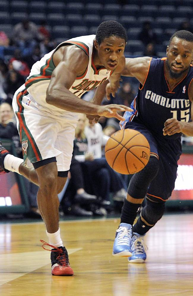 Milwaukee Bucks' Brandon Knight left, dribbles the ball past Charlotte Bobcats' Kemba Walker (15) during the second half of an NBA basketball game Saturday, Oct. 12, 2013, in Milwaukee