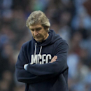Manchester City's manager Manuel Pellegrini stands on the touchline as his team is beaten 2-1 by Wigan in their English FA Cup quarterfinal soccer match at the Etihad Stadium, Manchester, England, Sunday, March 9, 2014
