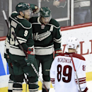 Arizona Coyotes left wing Mikkel Boedker (89), of Denmark, skates past as Minnesota Wild center Mikko Koivu (9) and right wing Jason Pominville (29) congratulate left wing Zach Parise (11) on an empty-net goal during the third period of an NHL hockey game