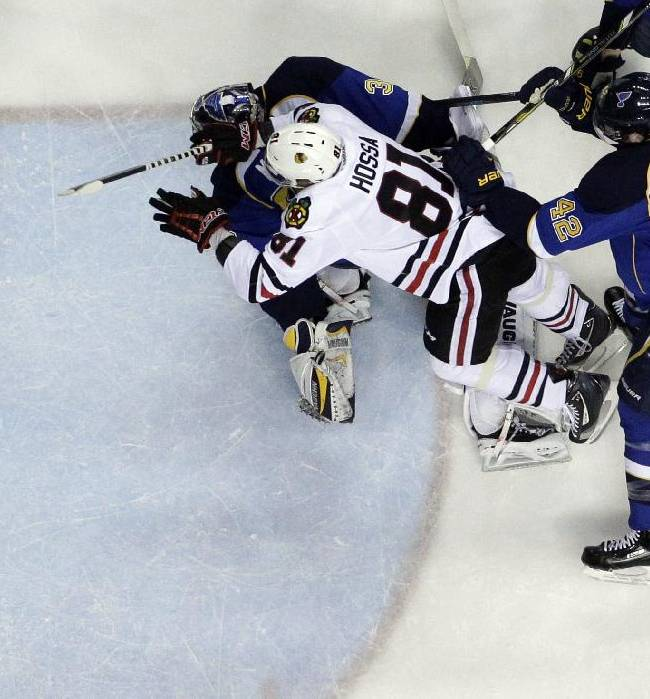 Chicago Blackhawks' Marian Hossa (81), of Slovakia, scores past St. Louis Blues goalie Ryan Miller and David Backes (42) during the first period in Game 5 of a first-round NHL hockey playoff series Friday, April 25, 2014, in St. Louis