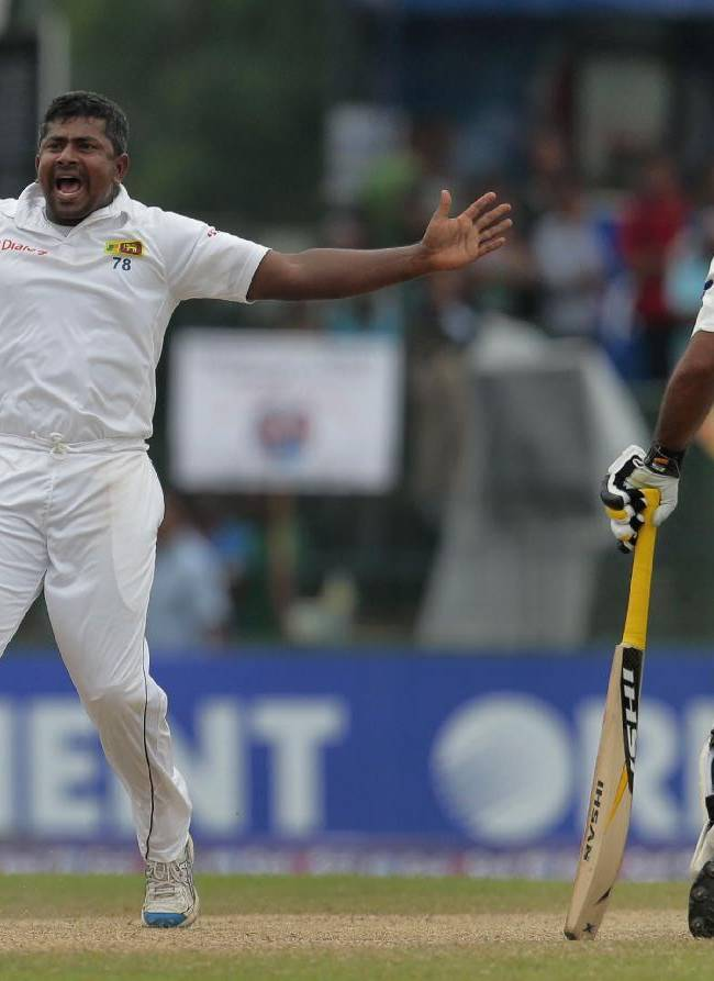 Sri Lanka's Rangana Herath, left, successfully appeals for the wicket of Pakistani batsman Younis Khan as non striker Asad Shafiq watches during the fourth day of their second test cricket match  in Colombo, Sri Lanka, Sunday, Aug. 17, 2014