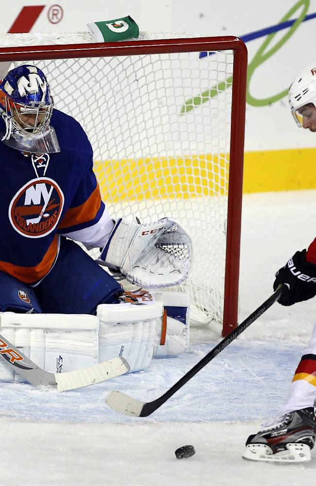 New York Islanders goalie Anders Nilsson, left, of Sweden, watches as Calgary Flames' TJ Galiardi gathers the puck to score during the second period of a split-squad preseason NHL hockey game in Calgary, Alberta, Tuesday, Sept. 17, 2013