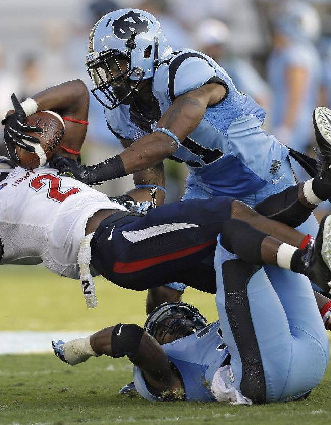 Liberty's D.J. Abnar (2) is tackled by North Carolina's Malik Simmons (11) and Sam Smiley during the first half of an NCAA college football game in Chapel Hill, N.C., Saturday, Aug. 30, 2014