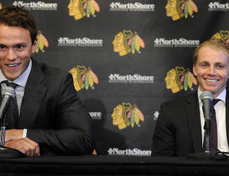Chicago Blackhawks players Jonathan Toews, left,  and Patrick Kane smile during a news conference at the United Center in Chicago, Wednesday, July 16, 2014. The Blackhawks recently agreed to eight-year contract extensions with for their star players.(AP Photo/Daily Herald, Mark Welsh)