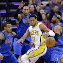 Indiana Pacers forward Danny Granger (33) loses control of the ball in front of, left to right, Dallas Mavericks guard Monta Ellis, forward Shawn Marion, and guard Vince Carter during the first half of an NBA basketball game in Indianapolis, Wednesday, Fe