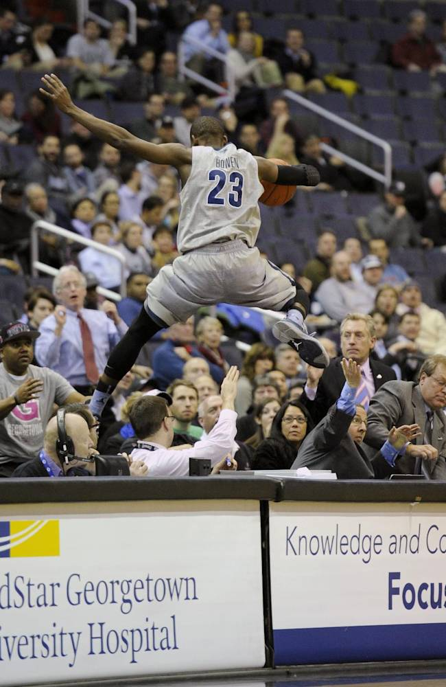 Georgetown forward Aaron Bowen (23) jumps over the scorers table as he chases after the ball during the first half of an NCAA college basketball game against Providence, Monday, Feb. 10, 2014, in Washington