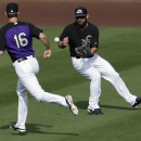 Colorado Rockies center fielder Jason Pridie, right, fields a single by San Francisco Giants' Brandon Hicks as center fielder Tim Wheeler (16) runs past during the ninth inning of an exhibition baseball game Tuesday, March 4, 2014, in Scottsdale, Ariz The