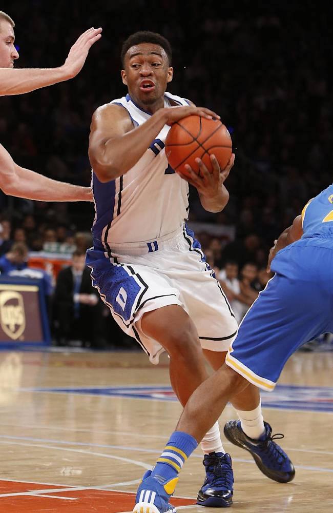 Duke's Jabari Parker, center, drives between UCLA's Travis Wear, left, and Norman Powell during the first half of an NCAA college basketball game, Thursday, Dec. 19, 2013, in New York