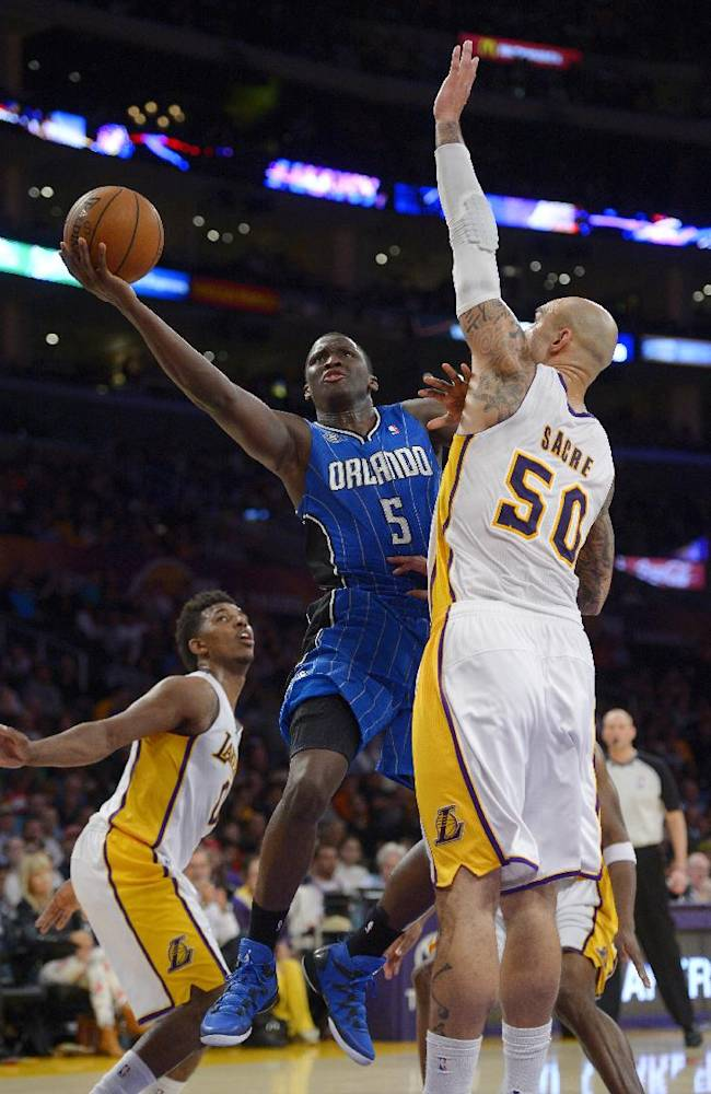 Orlando Magic guard Victor Oladipo, center, goes up for a shot as Los Angeles Lakers forward Nick Young, left, and center Robert Sacre defend during the second half of an NBA basketball game, Sunday, March 23, 2014, in Los Angeles. The Lakers won 103-94