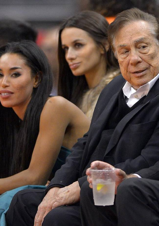 In this photo taken on Friday, Oct. 25, 2013, Los Angeles Clippers owner Donald Sterling, right, and V. Stiviano, left, watch the Clippers play the Sacramento Kings during the first half of an NBA basketball game in Los Angeles. The NBA is investigating a report of an audio recording in which a man purported to be Sterling makes racist remarks while speaking to his Stiviano.  NBA spokesman Mike Bass said in a statement Saturday, April 26, 2014, that the league is in the process of authenticating the validity of the recording posted on TMZ's website. Bass called the comments
