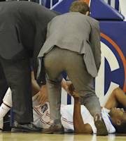 Florida's Kasey Hill (0) grimmaces as trainers help him after he was injured in the second half of an NCAA college basketball game against Southern University Monday, Nov. 18, 2013 in Gainesville, Fla. Florida defeated Southern University 67-53. (AP Photo/Phil Sandlin)