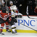 New Jersey Devils second goalie Cory Schneider holds up his glove on the bench to protect himself as Devils' Darius Zubrus, of Lithuania (8) collides with Boston Bruins' Brad Marchand (63) during the second period of an NHL hockey game in Newark, N.J., Su