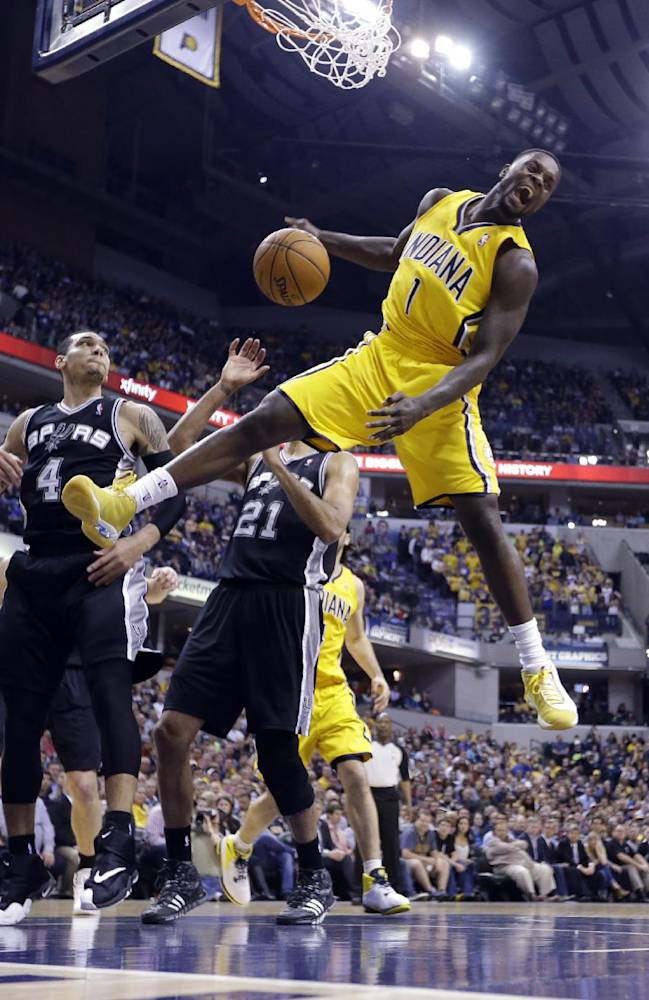 Indiana Pacers guard Lance Stephenson (1) reacts after a slam dunk over San Antonio Spurs guard Danny Green (4) and forward Tim Duncan (21) in the first half of an NBA basketball game in Indianapolis, Monday, March 31, 2014
