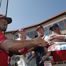 Philadelphia Phillies shortstop Jimmy Rollins, left, autographs a baseball for fans before a spring exhibition baseball game against the Atlanta Braves in Clearwater, Fla., Monday, March 10, 2014 The Associated Press
