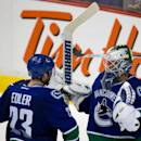 Vancouver Canucks' goalie Eddie Lack, right, and Alexander Edler, both of Sweden, celebrate after defeating the Calgary Flames 2-1 during an NHL hockey game in Vancouver, British Columbia, on Saturday March 8, 2014. (AP Photo/The Canadian Press, Darryl Dyck)