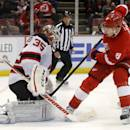 New Jersey Devils goalie Cory Schneider (35) stops a shot by Detroit Red Wings' Justin Abdelkader (8) during the second period of an NHL hockey game Friday, March 7, 2014, in Detroit. (AP Photo/Duane Burleson)