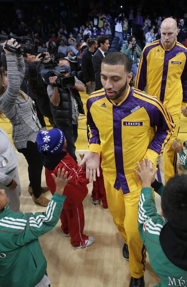 Members of Triqui kids basketball team, made up of children from the mountainous region of Oaxaca, Mexico, greet the Los Angeles Lakers before an NBA basketball game against the Minnesota Timberwolves in Los Angeles, Friday, Dec. 20, 2013