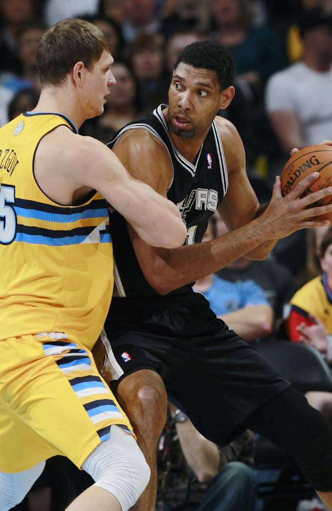San Antonio Spurs center Tim Duncan, right, works ball inside as Denver Nuggets center Timofey Mozgov, of Russia, covers in the first quarter of an NBA basketball game in Denver, Friday, March 28, 2014