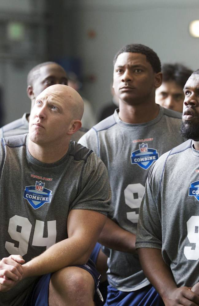 Carroll College defensive lineman Joshua Haasnoot (94) and Northern Alabama defensive lineman Brian Allen (91) listen to instructions at the broad jump station Saturday, March 22, 2014, during practice drills at an NFL football regional combine in Renton, Wash