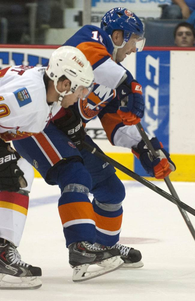 Calgary Flames center Corban Knight and New York Islanders defenceman Lubomir Visnovsky battle for the puck during third period NHL pre-season action on Tuesday, Sept. 17, 2013 in Regina, Saskatchewan. The Flames defeated the Islanders 4-2