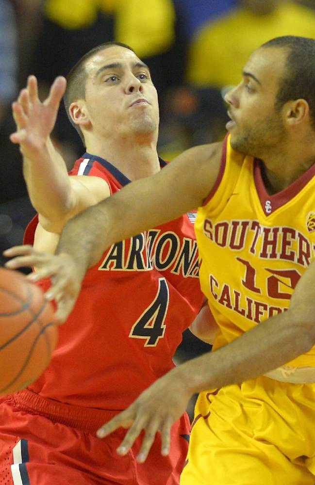 Southern California guard Julian Jacobs, right, passes under pressure from Arizona guard T.J. McConnell during the first half of an NCAA college basketball game, Sunday, Jan. 12, 2014, in Los Angeles