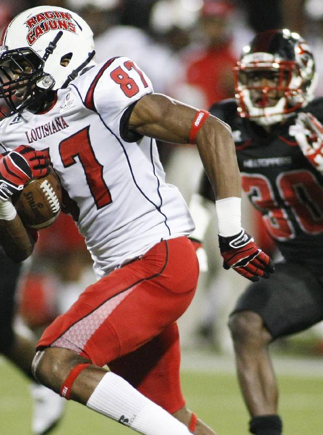 Louisiana-Lafayette wide receiver Darryl Surgent (87) carries the ball past Western Kentucky defensive back Prince Charles Iworah (30) during an NCAA college football game at Houchens-Smith Stadium on Tuesday, Oct. 15, 2013, in Bowling Green, Ky