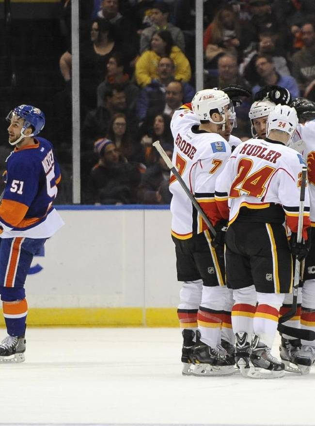 Calgary Flames' T.J. Brodie (7), Jiri Hudler (24) and Mikael Backlund (11) celebrate Dennis Wideman's goal as New York Islanders' Frans Nielsen (51) reacts in the second period of an NHL hockey game, Thursday, Feb. 6, 2014, in Uniondale, N.Y